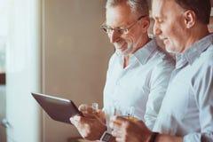 Amis âgés gais se reposant dans la cuisine Photos stock