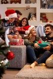 Amis échangeant des boîte-cadeau au réveillon de Noël Photos libres de droits