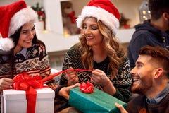Amis échangeant des présents au réveillon de Noël Images stock
