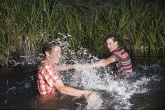 Amis éclaboussant l'eau à l'un l'autre Photographie stock