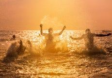 Amis éclaboussant l'eau en mer au coucher du soleil Photos libres de droits