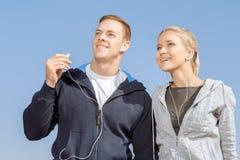 Amis écoutant la musique sur leurs écouteurs Images libres de droits