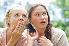 Amis écoutant un appel téléphonique Photo libre de droits