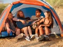 Amis écoutant une jolie fille jouant la guitare sur un fond naturel Camper avec des tentes Concept actif de style de vie Photos stock