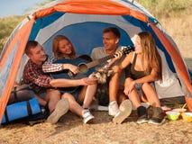 Amis écoutant une jolie fille jouant la guitare sur un fond naturel Camper avec des tentes Concept actif de style de vie Images stock