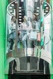 Amis élégants avec des paniers dans l'ascenseur dans le centre commercial Image stock