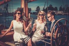 Amis élégants ayant l'amusement sur un yacht Image libre de droits