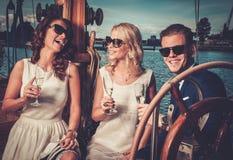 Amis élégants ayant l'amusement sur un yacht Photos stock
