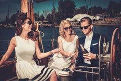 Amis élégants ayant l'amusement sur un yacht Image stock