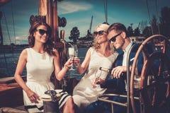 Amis élégants ayant l'amusement sur un yacht Photographie stock libre de droits