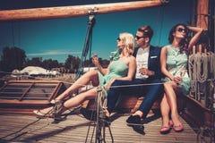 Amis élégants ayant l'amusement sur un yacht Photographie stock