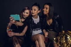 Amis élégants prenant le selfie ensemble pendant la partie d'isolement sur le noir Images stock