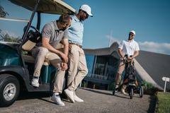 Amis élégants tenant le chariot de golf proche avant jeu Photo stock