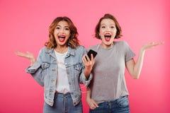Amis émotifs de femmes employant la musique de écoute de téléphone portable Image stock