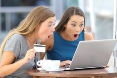 Amis étonnés achetant sur la ligne dans une barre Photo stock