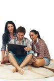 Amis étonnés avec l'ordinateur portatif Photographie stock libre de droits