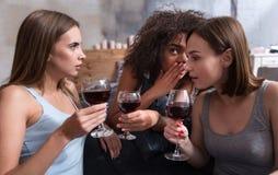 Amis étonnés buvant le vin et le bavardage Photographie stock