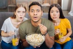Amis étonnés observant un film passionnant et mangeant du maïs éclaté Photo stock