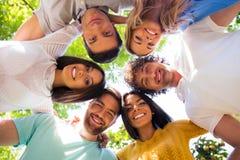 Amis étreignant ensemble au parc Image libre de droits