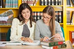 Amis étudiant au Tableau dans la bibliothèque Photographie stock libre de droits