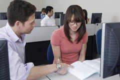 Amis étudiant ensemble dans le laboratoire d'ordinateur Image stock