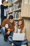 Amis étudiant ensemble sur l'ordinateur portable dans la bibliothèque Photo libre de droits