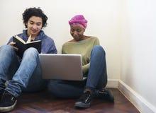 Amis étudiant ensemble utilisant l'ordinateur portable Photos stock
