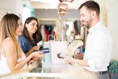 Amis achetant des bijoux avec la carte de crédit Image libre de droits
