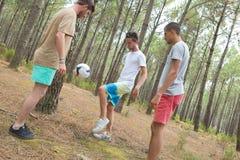Amis actifs jouant le football au déjeuner de pique-nique Photos stock