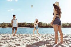 Amis actifs jouant le volleyball sur la plage ensemble Image stock
