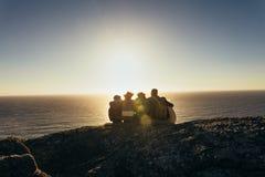 Amis admirant le coucher du soleil à partir du dessus de montagne Photo stock