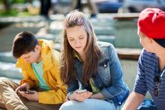Amis adolescents avec des smartphones dehors Photographie stock libre de droits