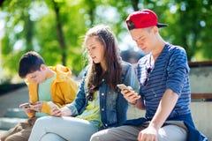 Amis adolescents avec des smartphones dehors Photographie stock