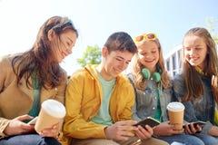 Amis adolescents avec des tasses de smartphone et de café Images stock