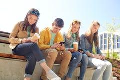 Amis adolescents avec des tasses de smartphone et de café Image stock