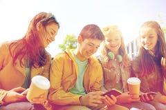 Amis adolescents avec des tasses de smartphone et de café Photo stock