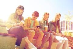Amis adolescents avec des tasses de smartphone et de café Photographie stock