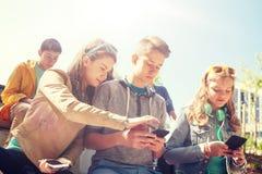 Amis adolescents avec le smartphone et les écouteurs Photographie stock libre de droits