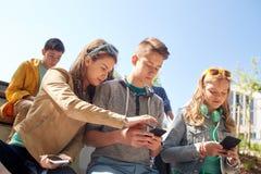 Amis adolescents avec le smartphone et les écouteurs Photo stock