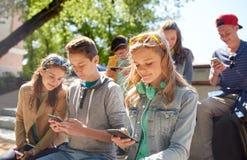 Amis adolescents avec le smartphone et les écouteurs Image stock