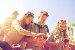 Amis adolescents avec le smartphone et les écouteurs Photographie stock