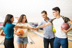 Amis adolescents de sourire empilant des mains au club de bowling Photographie stock