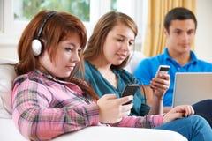 Amis adolescents employant la technologie numérique à la maison Photographie stock libre de droits