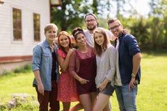 Amis adolescents heureux étreignant au jardin d'été Photographie stock