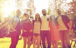 Amis adolescents heureux étreignant au jardin d'été Photo stock