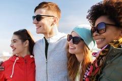Amis adolescents heureux aux nuances étreignant dehors Images libres de droits