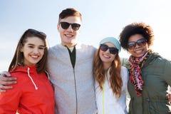Amis adolescents heureux aux nuances étreignant dehors Images stock