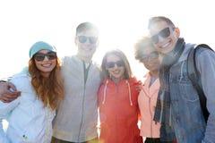 Amis adolescents heureux aux nuances étreignant sur la rue Photographie stock libre de droits