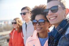 Amis adolescents heureux aux nuances étreignant sur la rue Photos stock