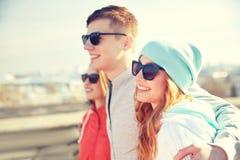 Amis adolescents heureux aux nuances étreignant sur la rue Image libre de droits